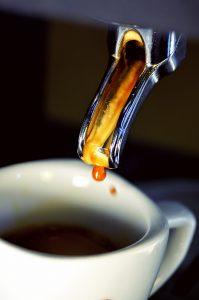 Espresso brewing into a white coffee cup
