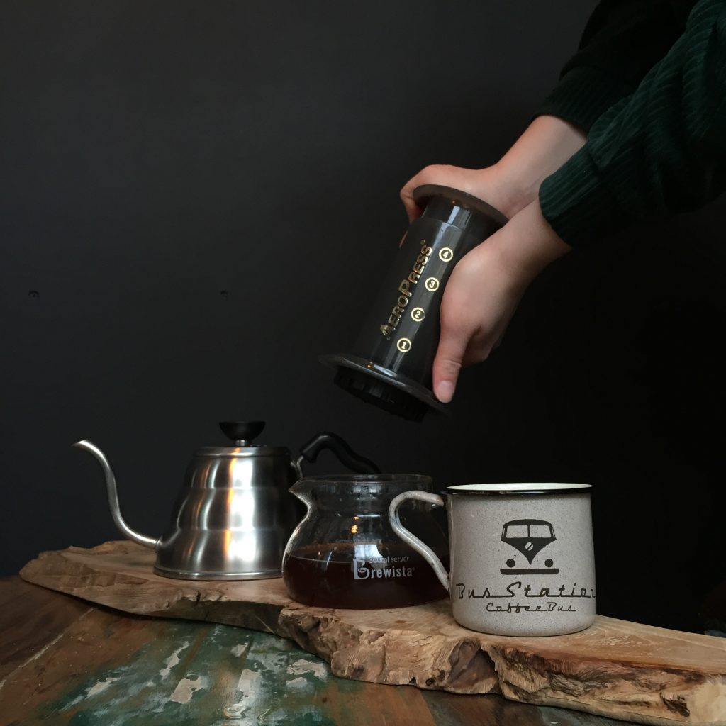 Person About to Put Aeropress Top Into Carafe