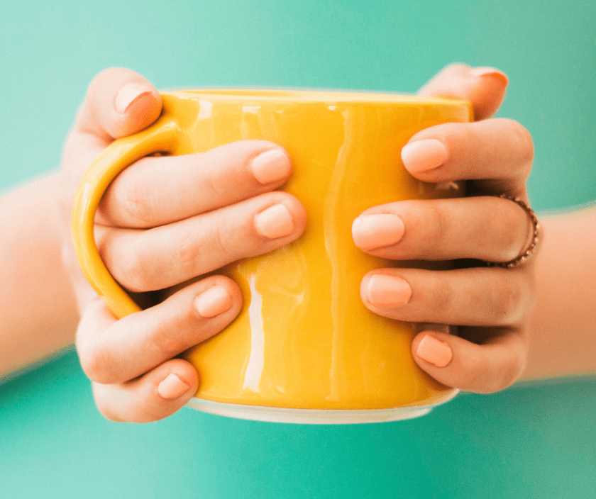 Yellow coffee mug being held with two hands