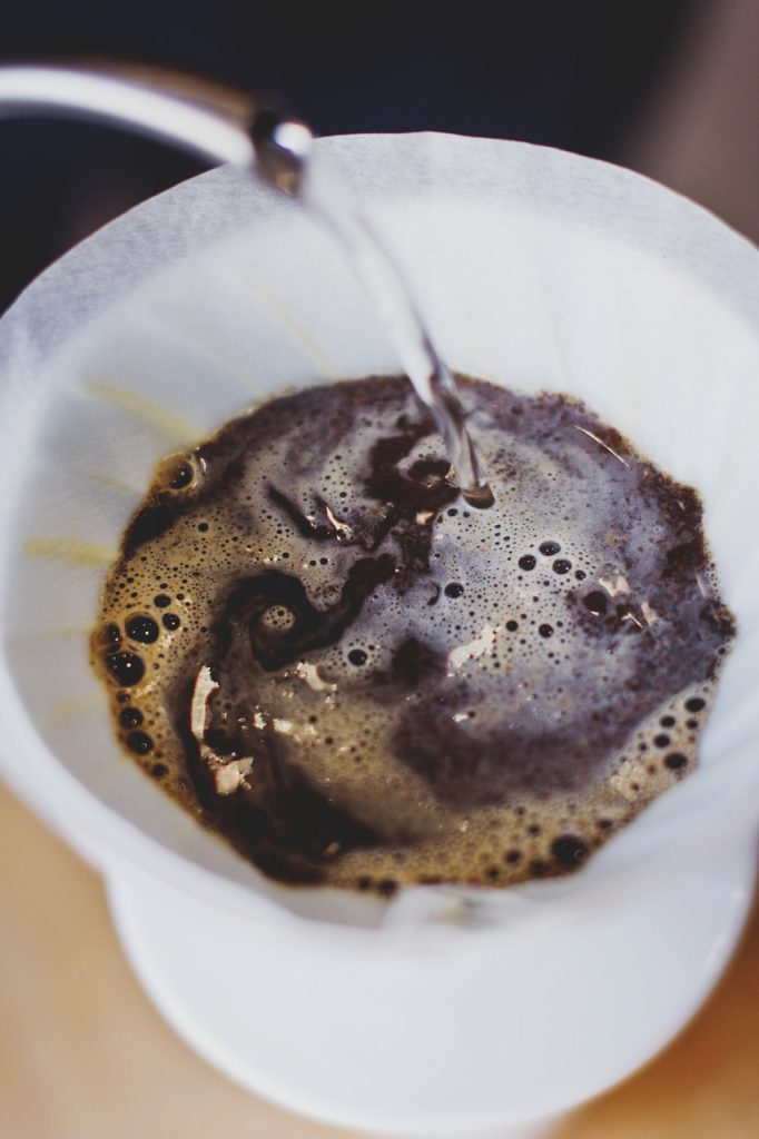 Pour over kettle with water flowing over coffee grounds