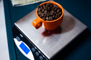Digital coffee scale weighing coffee beans in an orange mug