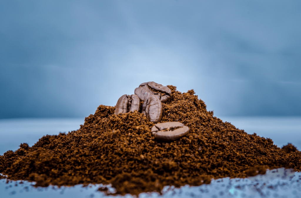Coarse ground coffee in a mound with whole beans