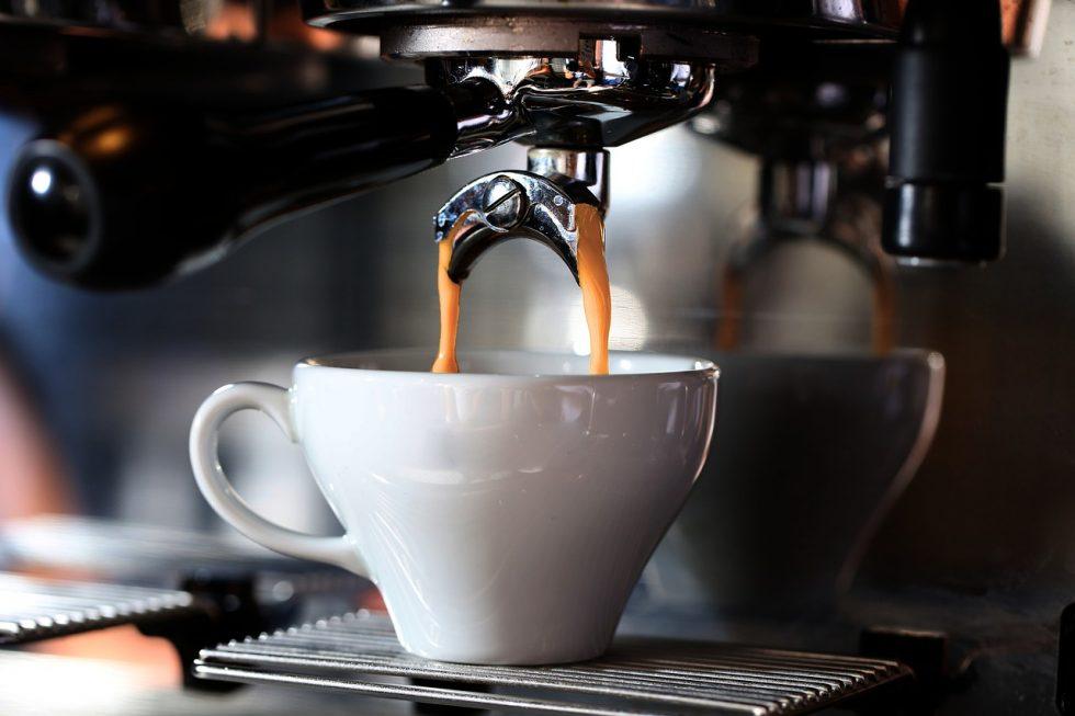 Cappuccino machine brewing into a white mug