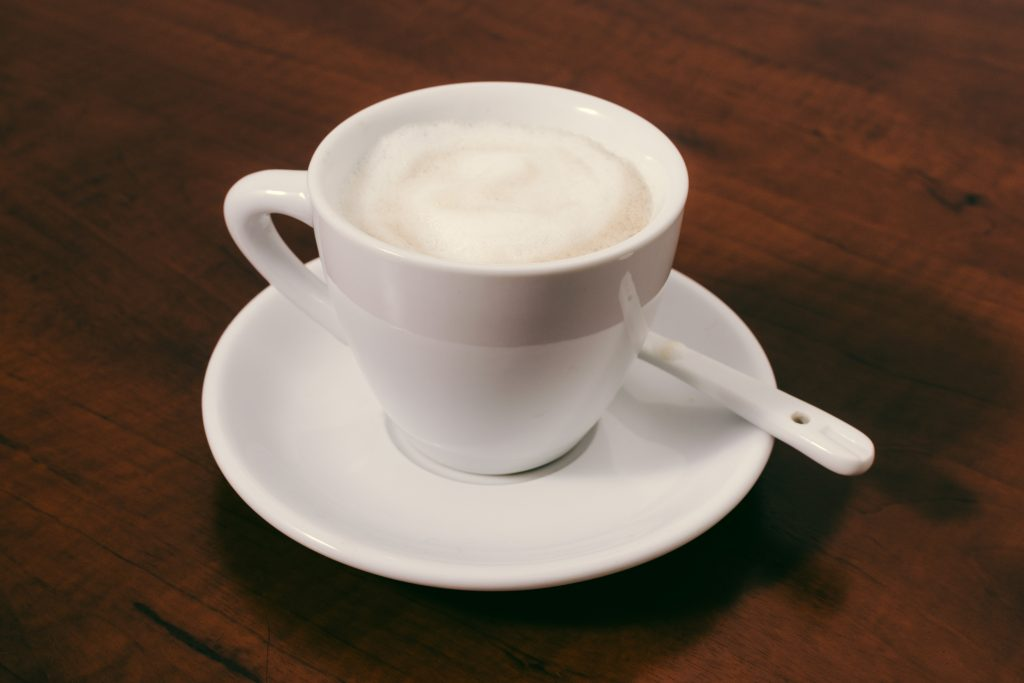 Frothed milk in a white cup on a saucer