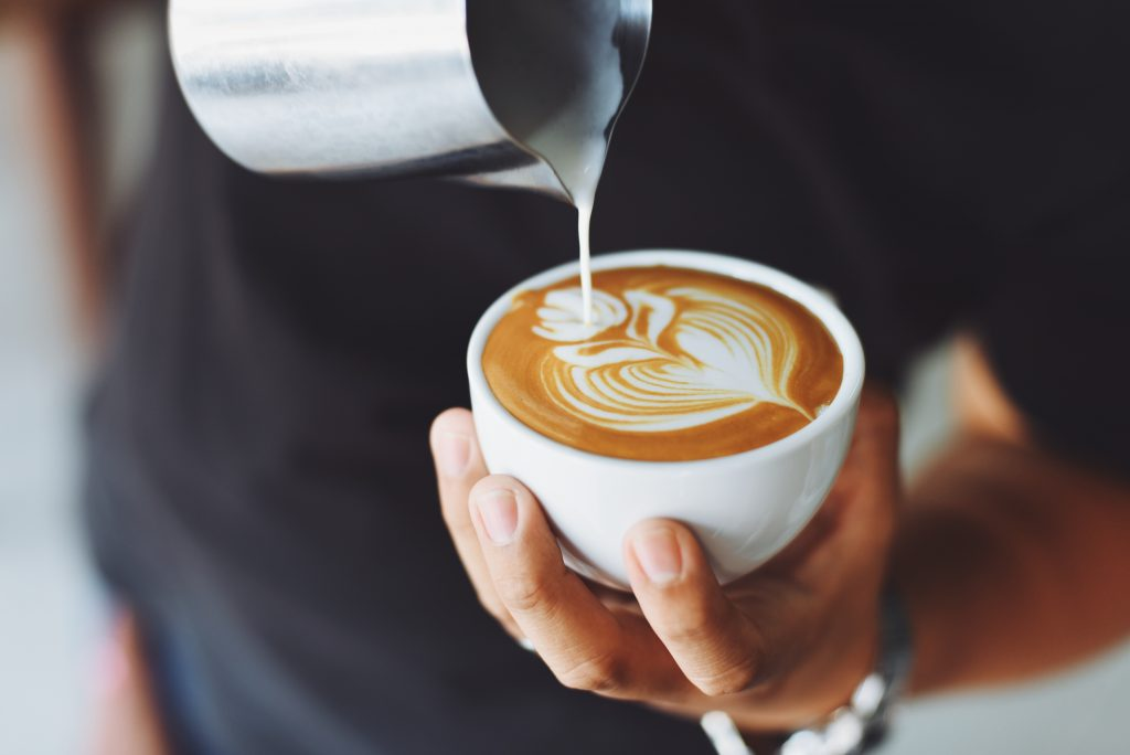 Person Pouring Steamed Milk Creating Latte Art