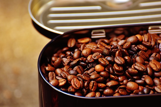 Roasted coffee beans in a black tin with the lid open