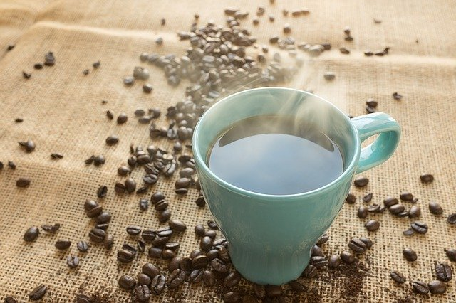 Light Blue Mug Filled With Coffee Surrounded By Whole Coffee Beans